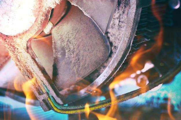 Ventilador do refrigerador sujo da unidade do computador com poeira dentro e chamas. conceito de peças de computador queimadas