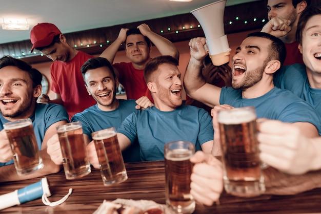 Ventiladores azuis da equipe que comemoram e que cheering na barra.