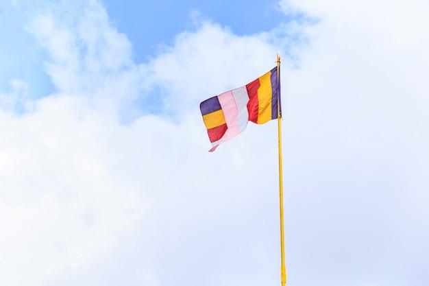 Vento balançando colorida bandeira budista no templo budista com fundo de céu azul em branco