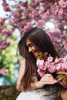Vento sopra cabelo de mulher morena enquanto ela coloca antes de uma árvore de sakura florescendo