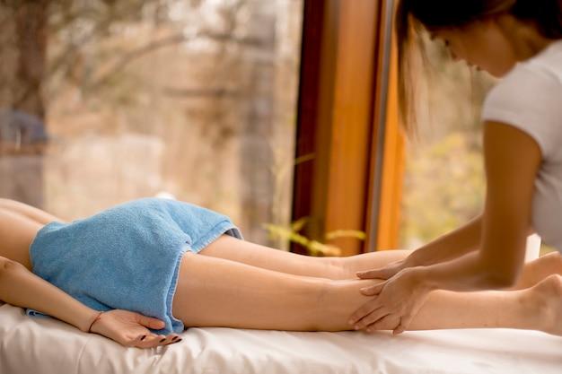Ver a bela mulher loira, desfrutando de uma massagem no spa de saúde