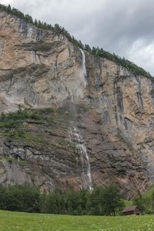 Ver a cachoeira do close up staubbach cair nas montanhas, vale das cachoeiras no parque nacional de lauterbrunnen, suíça, europa. paisagem de verão, clima ensolarado, céu azul dramático e dia ensolarado
