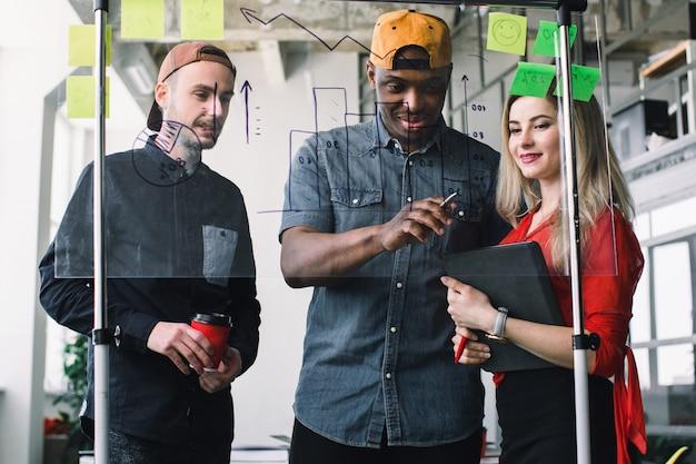Ver através de uma parede de vidro. homem africano criativo e homem caucasiano e mulher usam post-it notes para compartilhar a idéia.