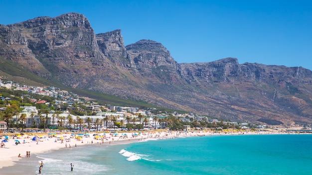 Ver camps bay bela praia com águas turquesas e montanhas na cidade do cabo, áfrica do sul