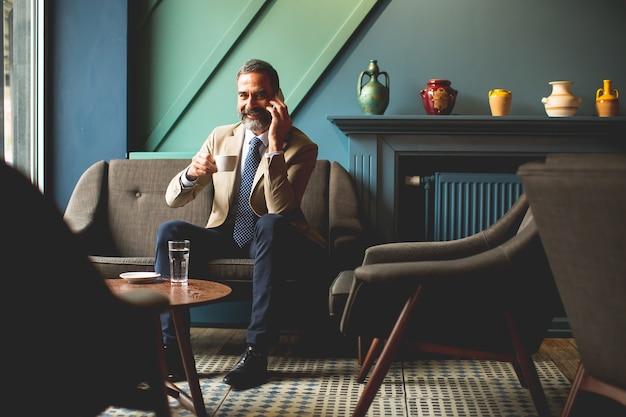 Ver em empresário de meia-idade, bebendo café e usando telefone celular no loby