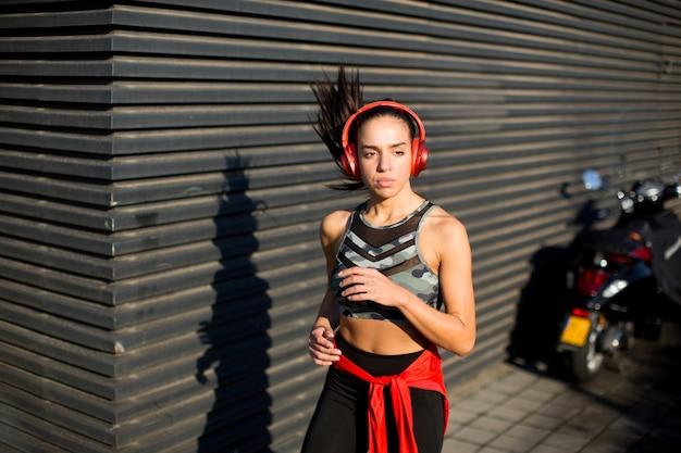 Ver em jovem mulher bonita ativa correndo em área urbana por noite