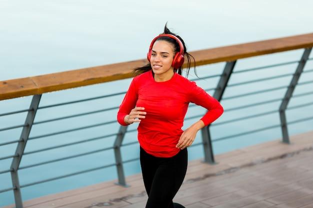 Ver em mulher jovem e bonita ativa correndo no passeio ao longo do lado do rio