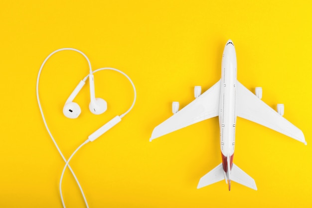 Ver os de cima no avião e fones de ouvido em forma de coração na mesa amarela.