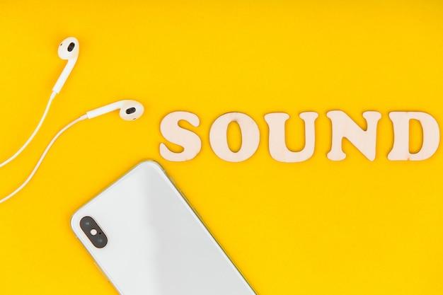 Ver os de cima no telefone, fones de ouvido e palavra som sobre o fundo amarelo.