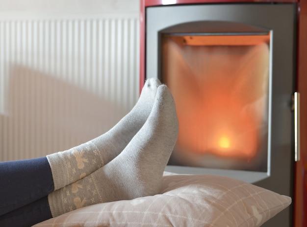Ver os pés de uma mulher em meias relaxantes em frente ao calor de um fogão a lenha