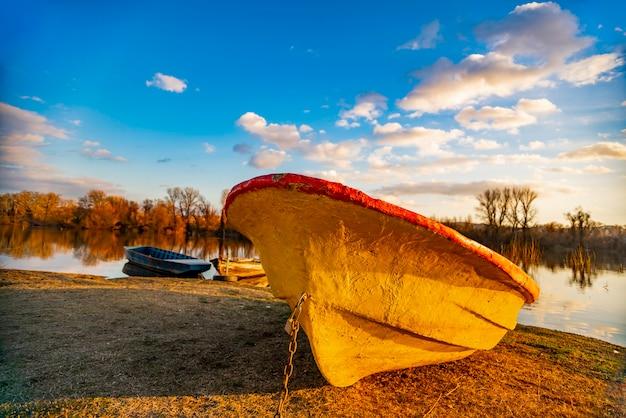 Ver um velho barco amarelo no chão perto do lago