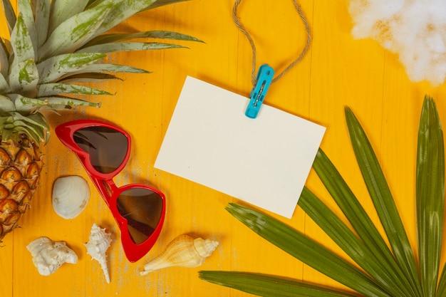 Verão com conchas, copos, frutas e papel em um amarelo