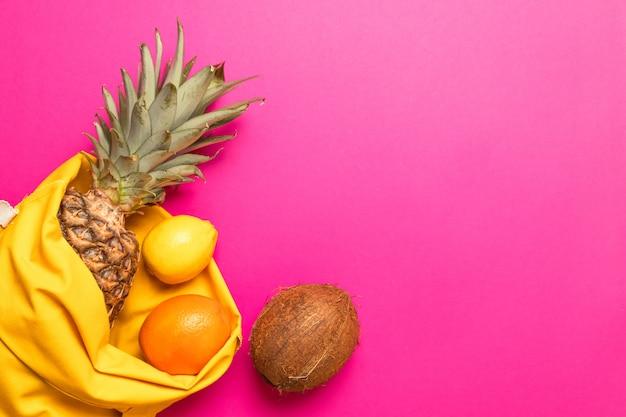 Verão, conceito de férias. frutas tropicais com um saco de algodão amarelo sobre um fundo rosa