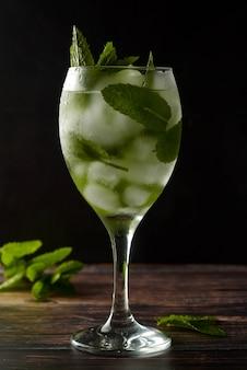 Verão coquetel ou bebida em copo de vinho. bebida refrescante com folhas de hortelã, gin tônica, xarope.