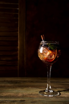Verão de baga vermelha cocktail com açúcar mascavo, mirtilos e gelo no backgorund de madeira escura