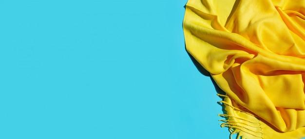 Verão de cachecol amarelo sobre fundo azul. copie o espaço