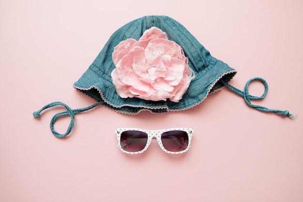 Verão denim infantil chapéu e óculos escuros em fundo rosa