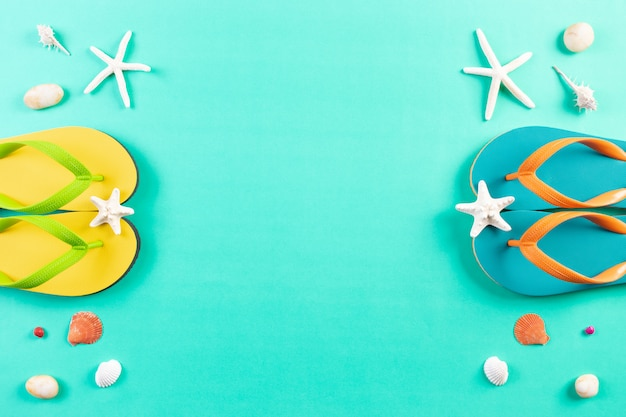 Verão. dois chinelos, estrelas do mar e conchas sobre fundo verde pastel. show mantenha sua distância.