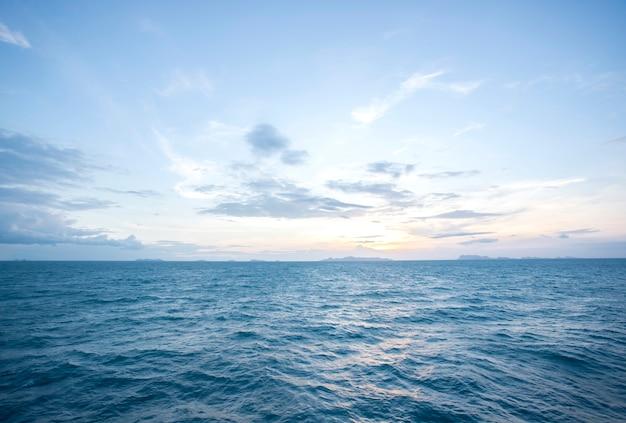 Verão e céu azul com ondas azuis do mar superfície macia e pôr do sol de beleza, tailândia