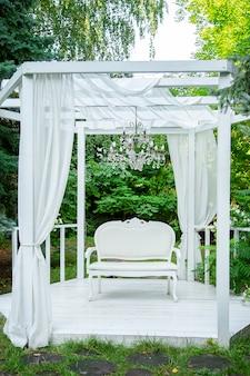 Verão elegante gazebo elegante nos jardins luxuriantes. gazebo clássico requintado do sofá.