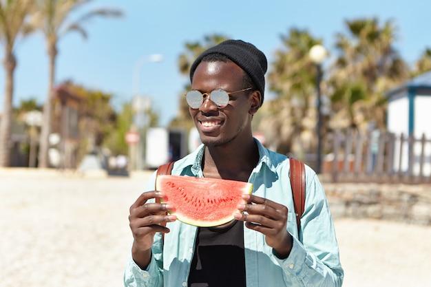 Verão, férias, feriados e estilo de vida. despreocupado feliz jovem viajante masculino de pele escura, fazendo um pequeno piquenique com os amigos à beira-mar, comendo suculenta deliciosa melancia