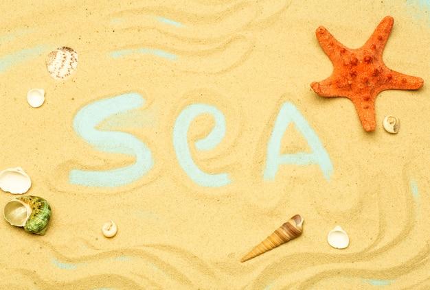 Verão, férias na praia ao fundo do mar. a inscrição e a palavra «seaâ» na areia da praia num verão ensolarado. mar, oceano e relaxamento backgarund.
