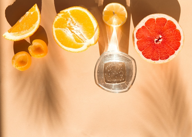 Verão flatlay fundo bege com água em copos e luz solar de frutas frescas