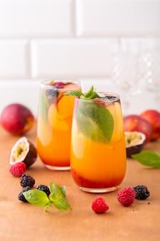 Verão frio cocktail de pêssego com manjericão, framboesa e amora