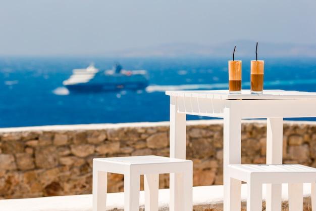 Verão gelado café frappuccino, frappe ou latte em um copo alto no bar da praia