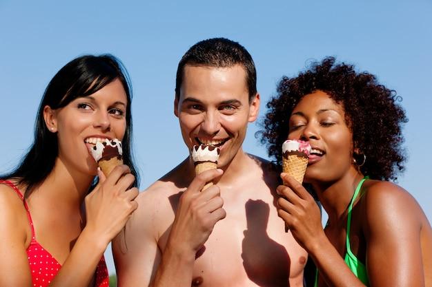 Verão - homem e duas mulheres comendo gelo na praia