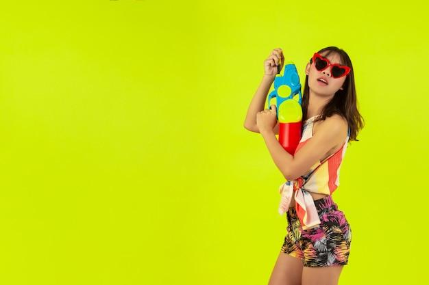 Verão linda jovem com pistola de água, férias songkran