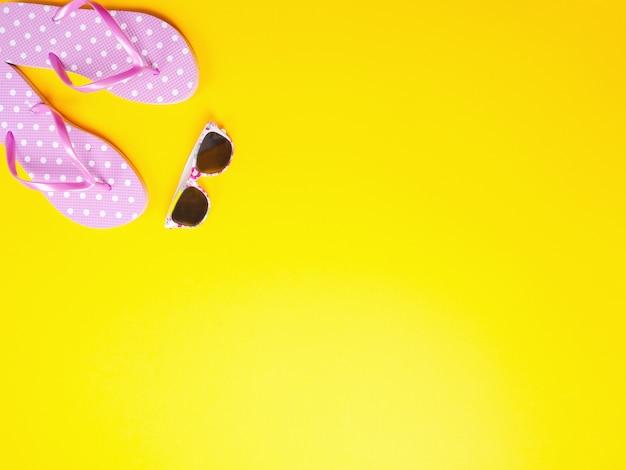 Verão plana leigos. encalhe chinelos e óculos de sol cor-de-rosa dos acessórios no fundo amarelo.
