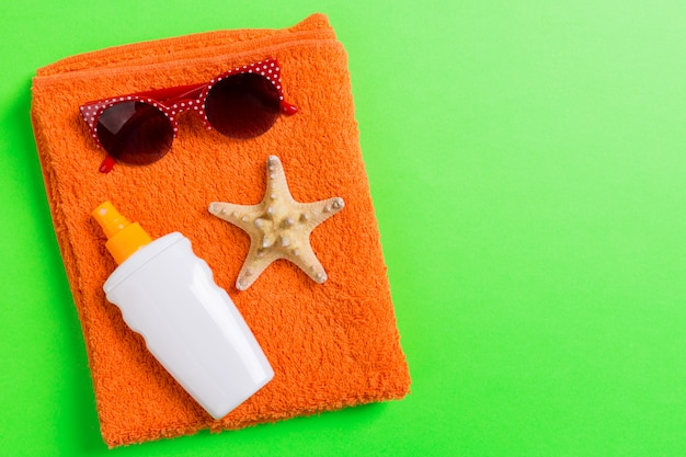Verão praia plana leigos acessórios. creme protetor solar garrafa, toalha e conchas sobre fundo colorido. conceito de férias viagens com espaço de cópia