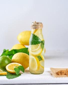 Verão refrescante bebida limonada com limão, folhas de hortelã, limão em uma garrafa de vidro