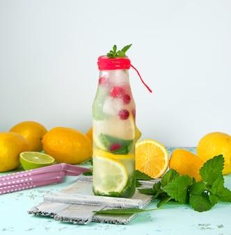 Verão refrescante bebida limonada com limões, amora, folhas de hortelã e limão em uma garrafa de vidro