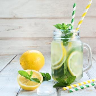Verão refrescante coquetel de desintoxicação. molhe com limão, hortelã e gelo no frasco de pedreiro na placa de madeira branca.