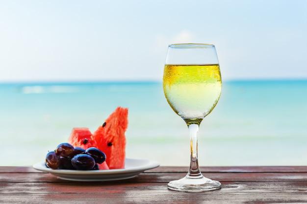 Verão, uma taça de champanhe e frutas contra o fundo do mar