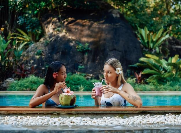 Verão viajando na tailândia. mulheres jovens em trajes de banho bebem coquetéis gelados e naturais e nadam na piscina.