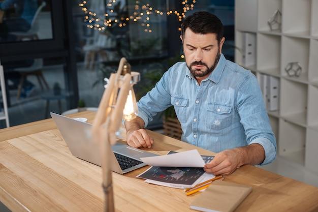 Verdadeiro workaholic. belo empresário inteligente e trabalhador, sentado à mesa e trabalhando com documentos, enquanto fica até tarde no trabalho