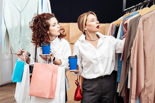 Verdadeiros compradores compulsivos. mãe e filha bonitas e elegantes sendo verdadeiras shopaholics chegando à nova loja