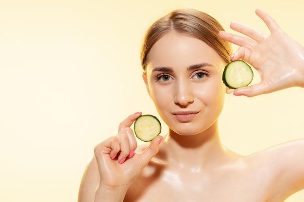 Verde close-up de lindo rosto feminino com fatias de pepino sobre cosméticos de fundo amarelo e