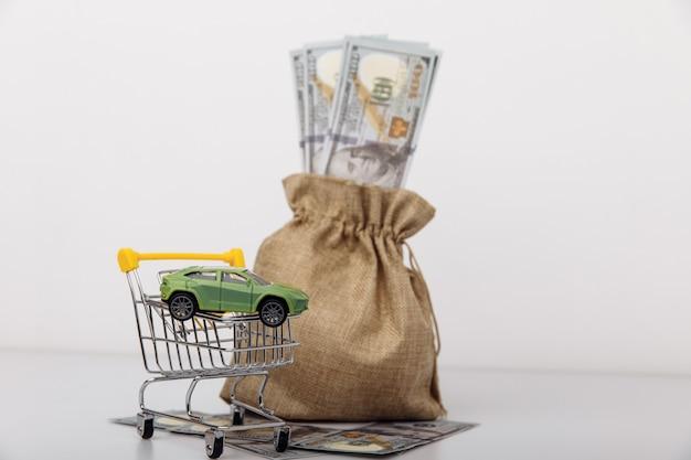 Verde de carro no carrinho de compras com saco de dinheiro em fundo branco