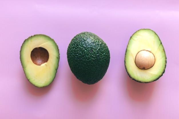Verde fresco cortado ao meio e abacate inteiro isolado em um fundo rosa, vista superior, close-up, espaço para texto.
