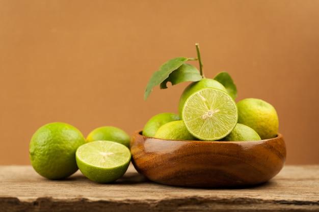Verde limão em bacias de madeira na mesa de madeira velha