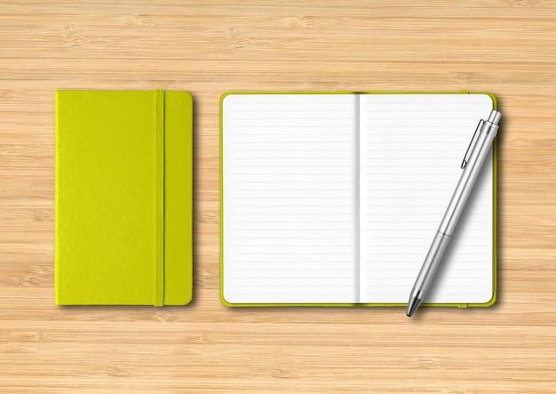 Verde-limão fechado e cadernos forrados abertos com uma caneta. isolado em fundo de madeira