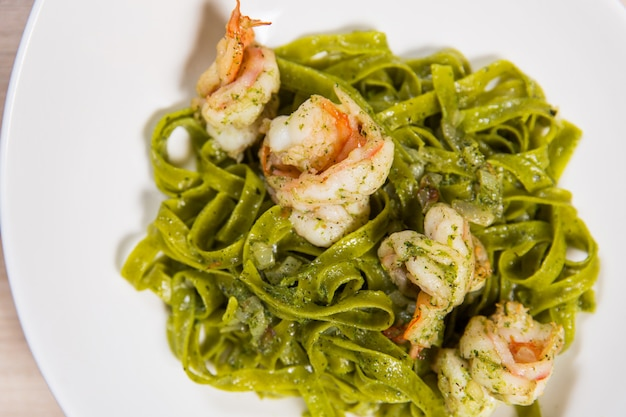 Verde, macarronada, com, camarões, e, queijo, em, prato branco, ligado, luz, tabela madeira, em, um, restaurante