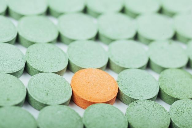 Verde médico e um comprimido laranja para o tratamento e cuidados de saúde em um fundo branco