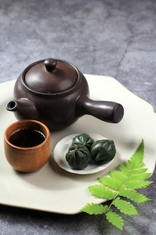 Verde mugwort kkultteok é bolo de arroz em forma de bola com mel e xarope de gergelim, bolo tradicional coreano para o dia do chuseok. servido com chá