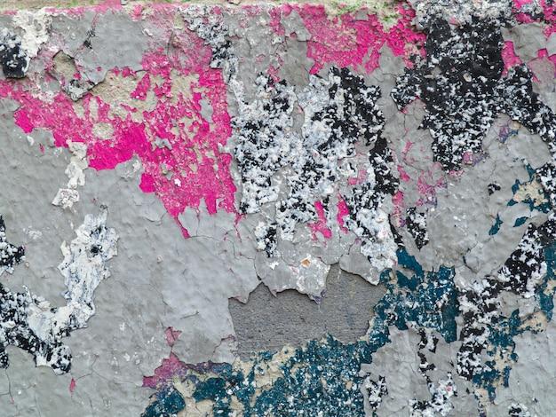 Verde, rosa, pintar no gesso rachado. parede em ruínas com salpicos de tinta multi-coloridas