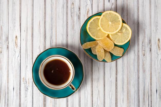 Verde xícara de chá quente e pires com limões e gengibre cristalizado em uma mesa de madeira. flatlay